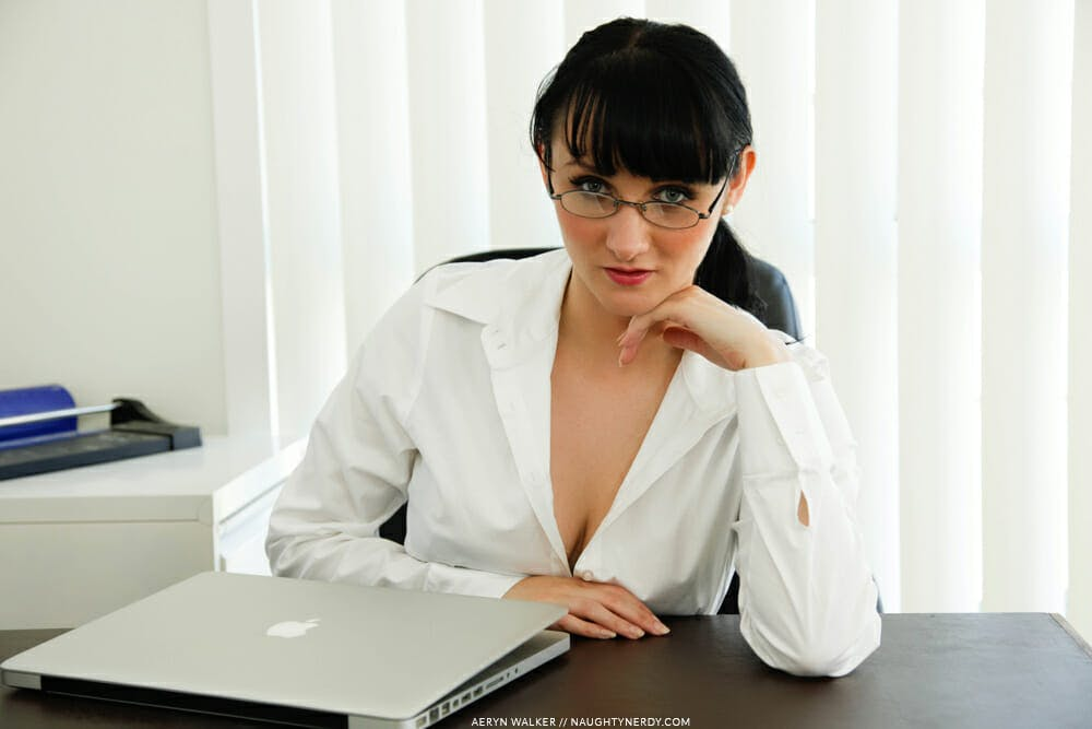 Image of a performer seductively staring into the camera from her desk.