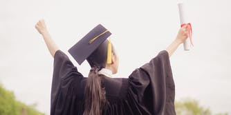 College Graduate Holding Up Diploma