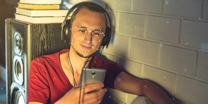 Man wearing headphones and using phone with facial recognition overlay