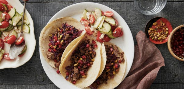 Greek lamb tacos with pomegranate seeds and cucumber-tomato salad