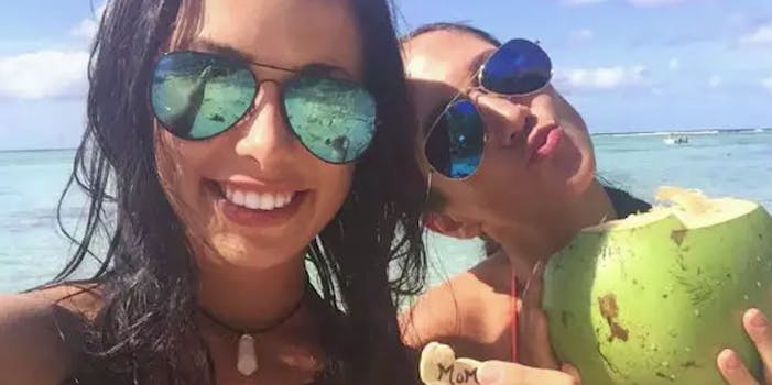 Two girls smile for a selfie in sunglasses, one holds a drink in a coconut