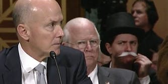 Person dressed as Uncle Moneybags Monopoly man watches Equifax Congressional hearing