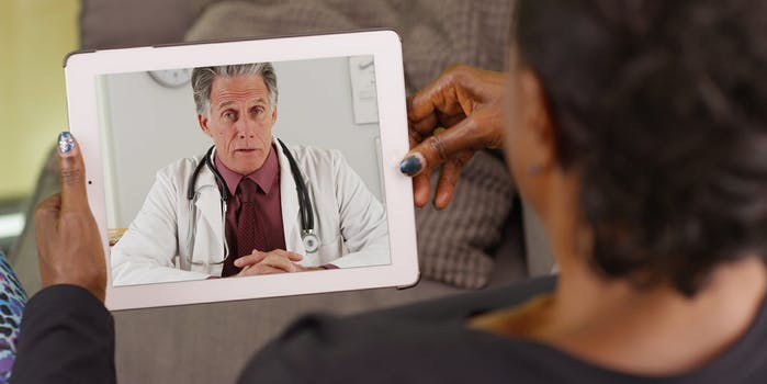 Older black woman chatting with doctor on iPad