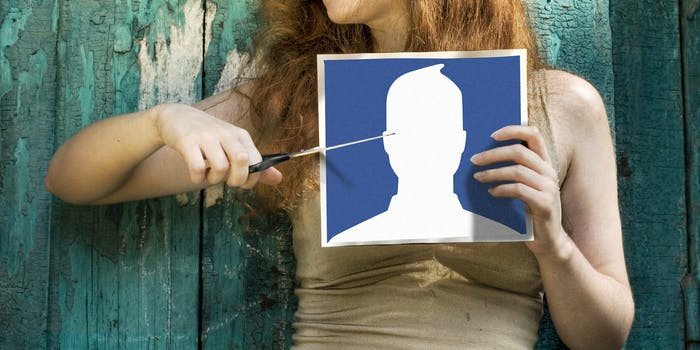 how to delete photos from facebook : Woman cutting Facebook icon photo with scissors