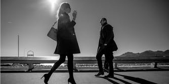 A woman and man walking next to each other in opposite directions