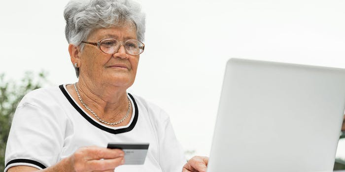 Elderly woman holding credit card while using laptop