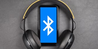 how does bluetooth work? Bluetooth logo on smartphone between wireless headphones