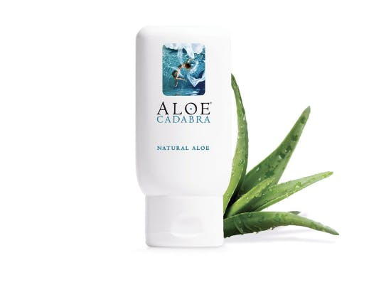 Aloe Cadabra natural aloe lube on a white background with an aloe leaf resting behind the product.