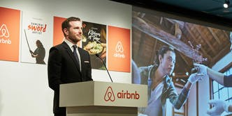Airbnb representative talking onstage