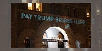 """A projected message onto the Trump International Hotel in Washington D.C. that reads """"Pay Trump Bribes Here."""""""