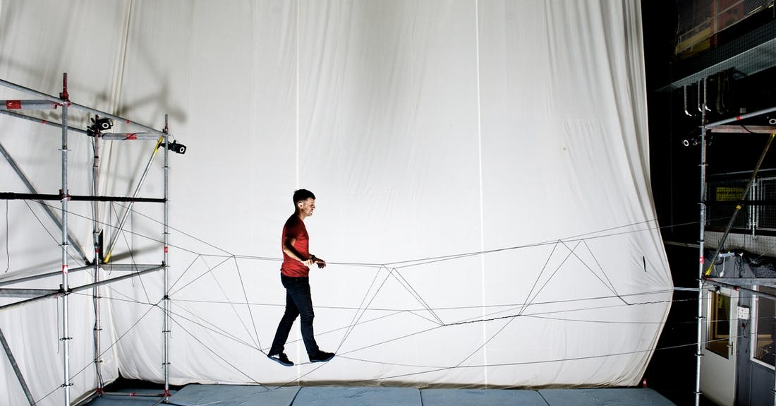 A person crosses a rope bridge woven by cooperating drones.