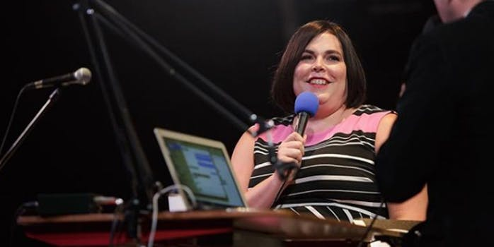 Shadi Petosky smiles holding a microphone while appearing on a podcast