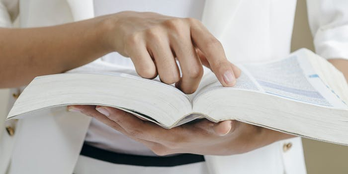 Woman pointing to definition in dictionary