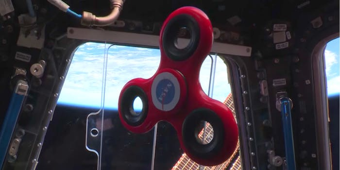 NASA international space station astronauts play with a fidget spinner in space.