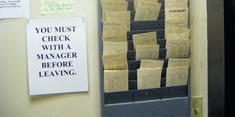 """Timecards next to a sign that says """"You must check with a manager before leaving"""""""