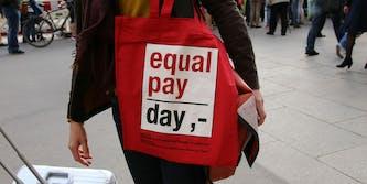 Red Equal Pay Day bag on shoulder