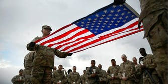 U.S. Military service members hold the U.S. flag.