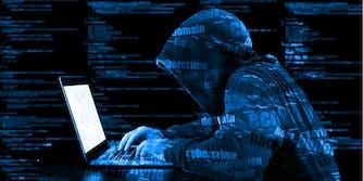 hacker on computer sitting at desk malware virus