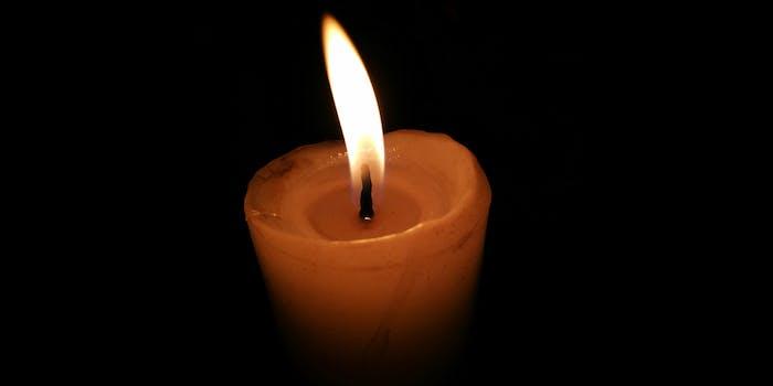single lit candle on black background