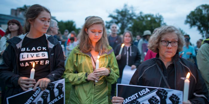 Three women stand with lit candles and anti-racist signs at a vigil for Charlottesville victims.