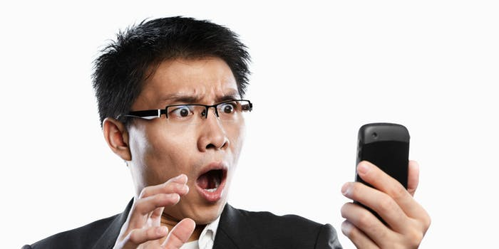 A man stares shocked at his phone screen.