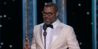 Jordan Peele giving his Oscars acceptance speech in a white tux and glasses