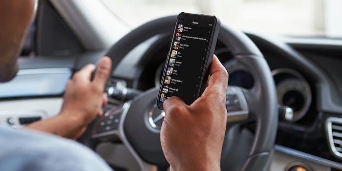 Man choosing Spotify playlist in driver's seat