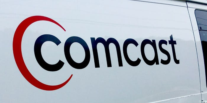 The Comcast logo on the side of a white van.