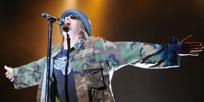 Kid Rock yelling into microphone with arms spread
