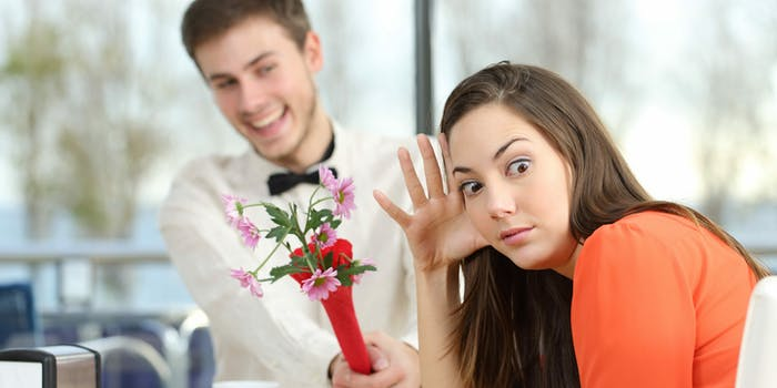 A woman rejecting a man giving her flowers.
