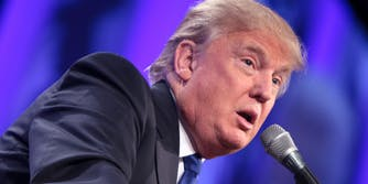 Donald Trump leaning over microphone