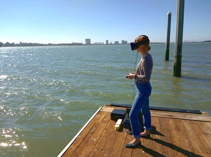 A person wearing a VR headset explores the depths below her via the Trident's camera.