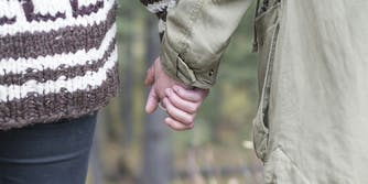 age of consent by state :A young couple holding hands while walking through the woods