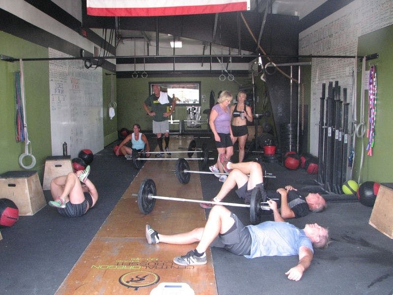 Crossfit gym members lying on floor
