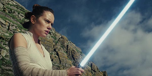Rey from Star Wars swinging a lightsaber