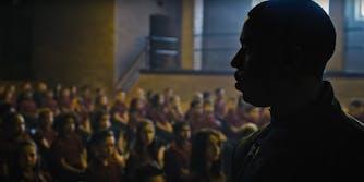 Michael B Jordan stands in front of a classroom of children