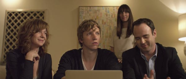 Four people sit around a laptop in a scene from what other couples do