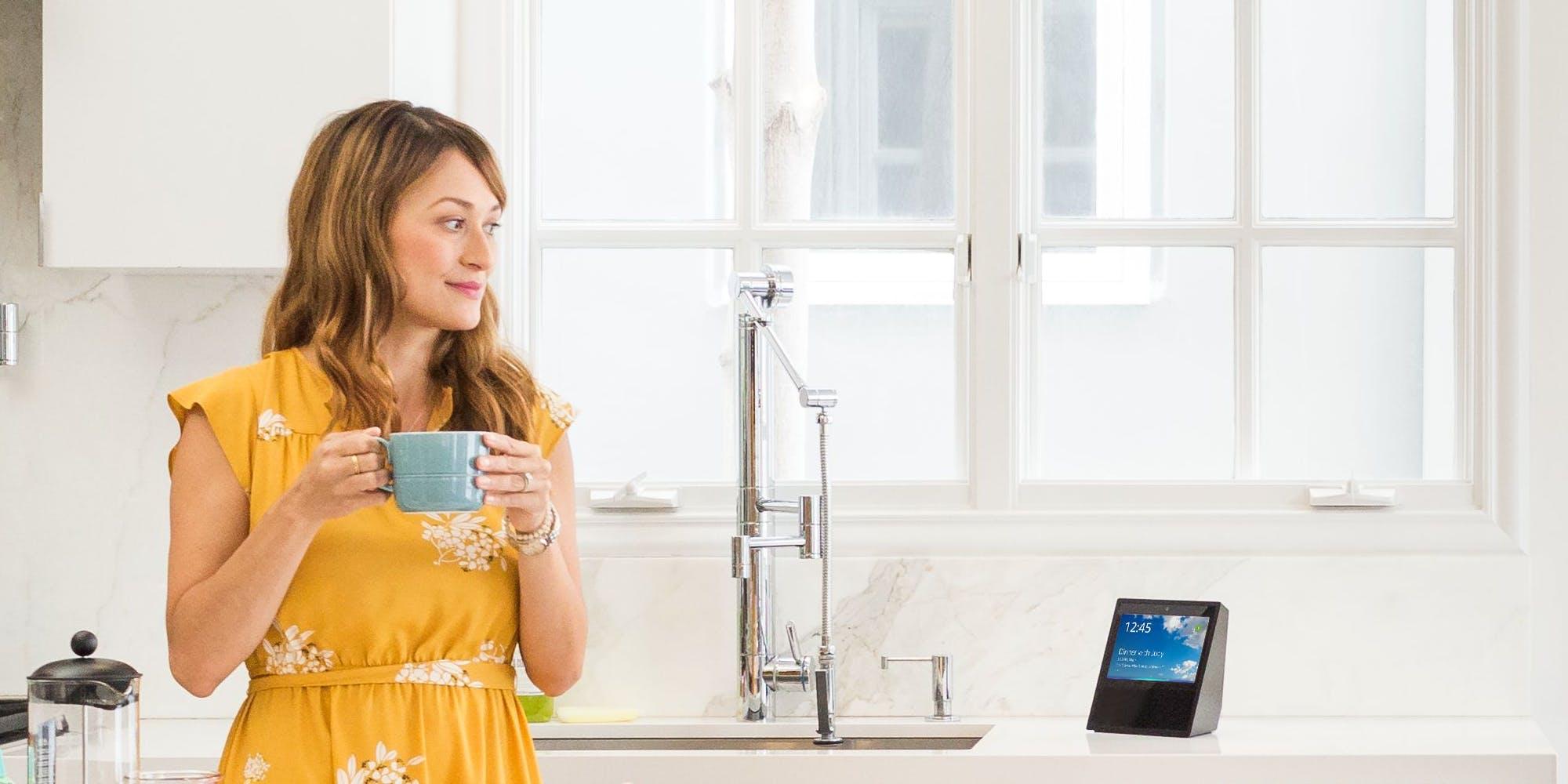 how to use Amazon Alexa: Woman looking towards Amazon Echo Show