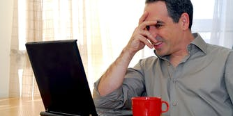 Man partially covering face while looking at laptop