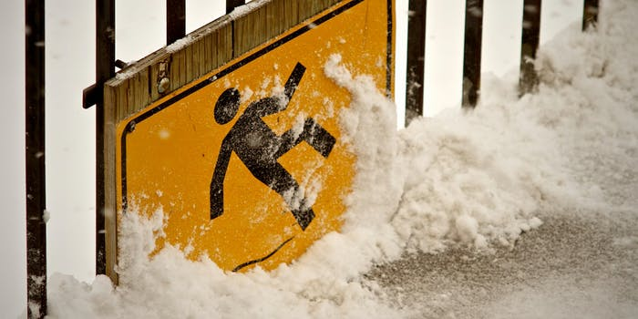 Warning sign of man slipping on ice on snowy deck