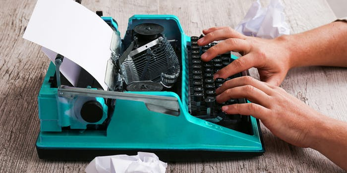 Man typing on blue typewriter with balled up sheets of paper on desk