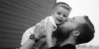 A dad kissing his baby daughter