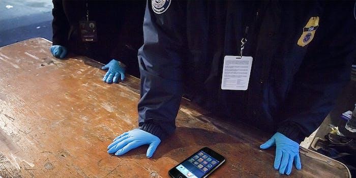 TSA screeners with blue gloves examine phone for social media accounts