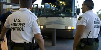 """Customs officers await a greyhound bus for inspection in shirts reading: """"U.S. Border Patrol."""""""