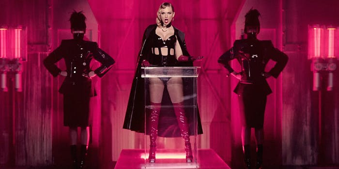 Taylor Swift in leather cape at podium