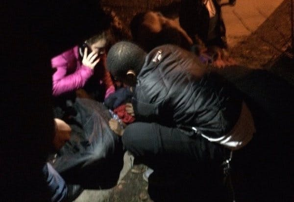 Protesters attend to a protester reportedly shot in the stomach. —