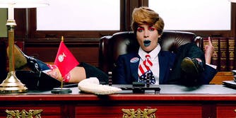 Singer from Pussy Riot sitting at desk dressed as Trump
