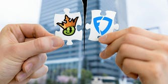 Photo of hands holding Draft Kings and Fanduel logos on matching puzzle pieces being torn apart