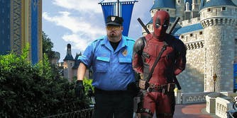 Deadpool being escorted out of Disney World by security guard