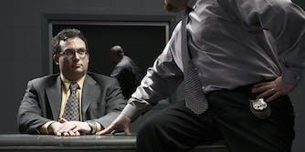 Man sitting at desk in interrogation room